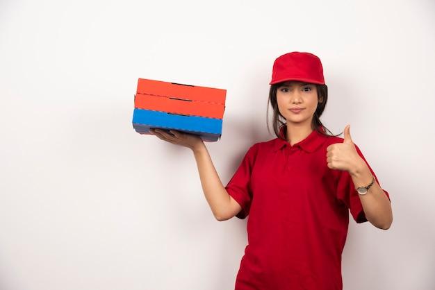 Jonge vrouwelijke pizzabezorger die zich met drie kartonnen pizza's bevindt.