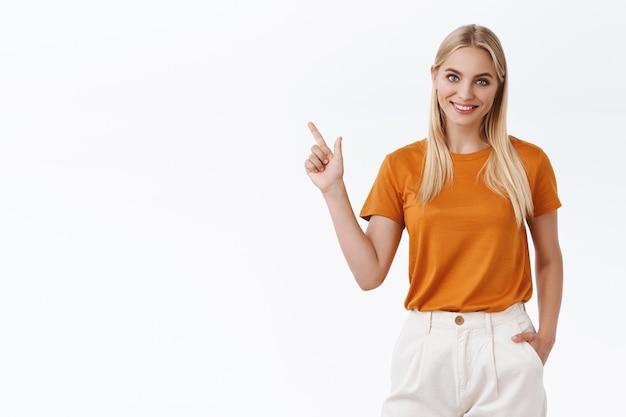 Jonge vrouwelijke professionele aanwijskaart. aantrekkelijk blond meisje met blauwe ogen, tatoeages, hand in hand in broek zorgeloos, linker bovenhoek tonen, vreugdevol glimlachen, advies geven, met vermelding van promo