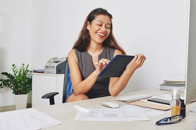 Jonge vrouwelijke projectmanager lachen mock-ups van mobiele applicatie controleren en presentatie van project op tabletcomputer bekijken