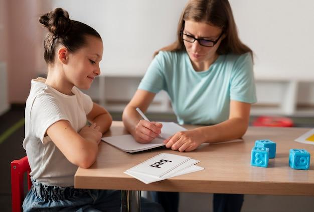 Jonge vrouwelijke psycholoog die een meisje helpt bij logopedie