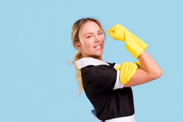Jonge vrouwelijke reinigingsmachine die haar spier toont tegen blauwe muur
