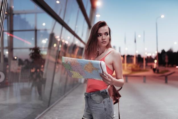 Jonge vrouwelijke reiziger die de kaart vasthoudt en 's avonds de plaats doorzoekt