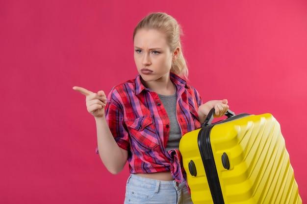 Jonge vrouwelijke reiziger die de rode koffer van de overhemdsholding op geïsoleerde roze muur draagt