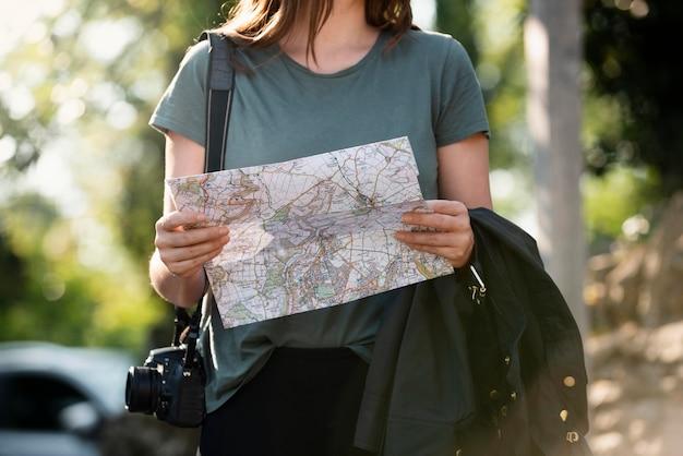 Jonge vrouwelijke reiziger die een kaart controleert
