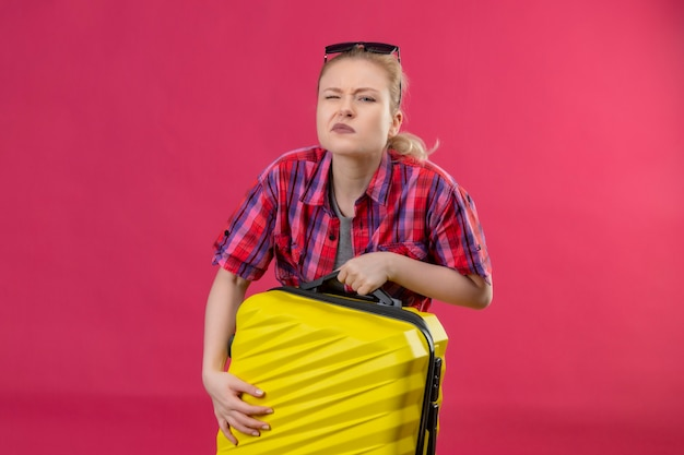 Jonge vrouwelijke reiziger die een rood overhemd en een bril op haar hoofd draagt en een zware koffer op geïsoleerde roze muur houdt