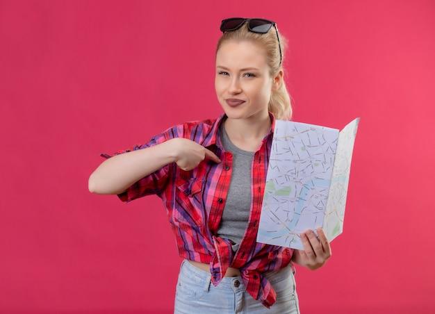 Jonge vrouwelijke reiziger die een rood overhemd en een bril op haar hoofd draagt en kaart houdt wijst naar zichzelf op geïsoleerde roze muur