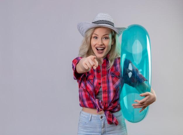 Jonge vrouwelijke reiziger die rood overhemd in hoed draagt die opblaasbare ring houdt die u gebaar op geïsoleerde witte muur toont