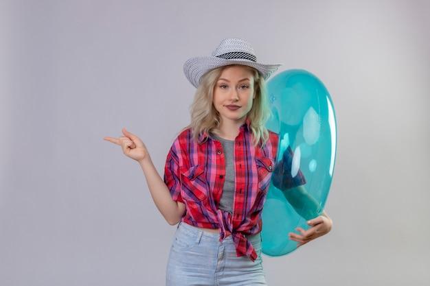 Jonge vrouwelijke reiziger die rood overhemd in hoed draagt die opblaasbare ring houdt wijst naar kant op geïsoleerde witte muur
