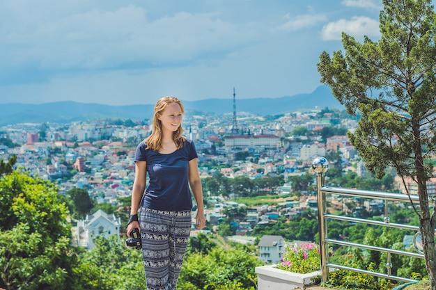 Jonge vrouwelijke reiziger genieten van geweldig uitzicht over de stad dalat, vietnam