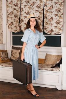 Jonge vrouwelijke reiziger in witte hoed die in de kamer staat met bagage.
