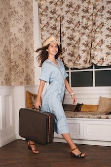 Jonge vrouwelijke reiziger in witte hoed wandelen in de kamer met bagage.