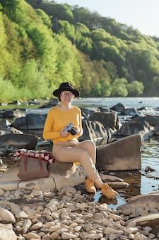 Jonge vrouwelijke reiziger maakt foto's van de natuur op retro camera