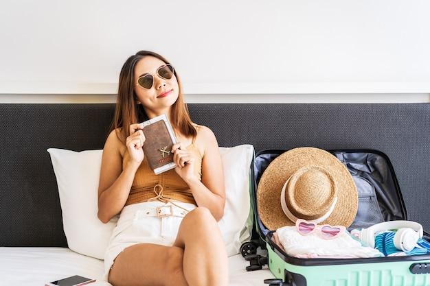Jonge vrouwelijke reiziger met paspoort is blij dat ze kunnen reizen en bagage kunnen voorbereiden op de zomervakantie