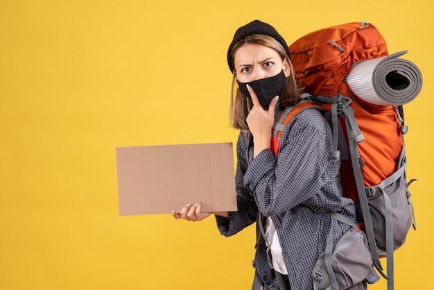 Jonge vrouwelijke reiziger met zwart masker en rugzak met karton