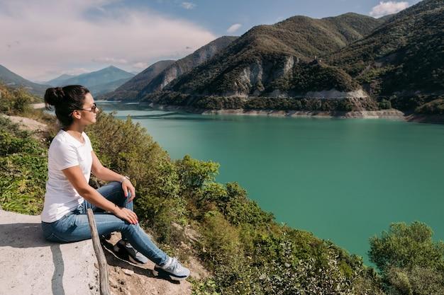 Jonge vrouwelijke reiziger zit en kijkt naar een prachtig uitzicht op het zhinvalskoe reservoir, georgia.