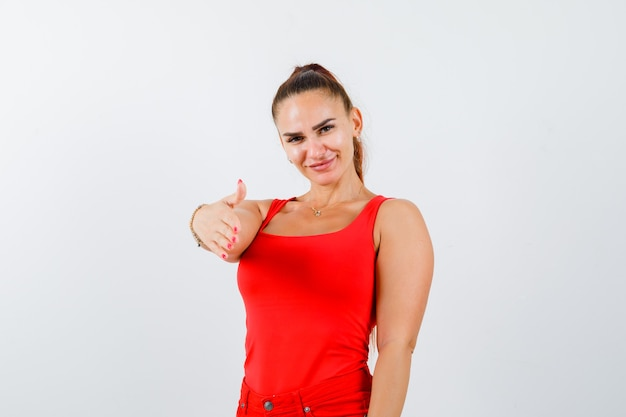 Jonge vrouwelijke rekhand voor groet in rode tanktop, broek en ziet er mooi uit, vooraanzicht.