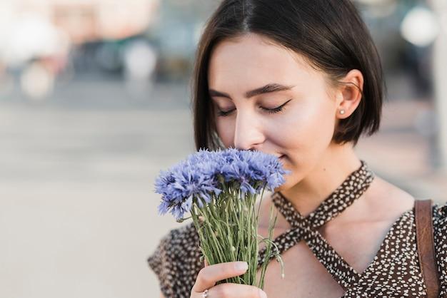 Jonge vrouwelijke ruikende bloemen
