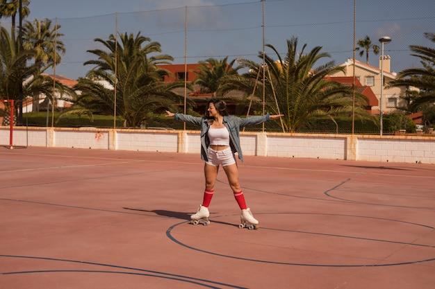 Jonge vrouwelijke schaatser die op een openluchthof uitoefent