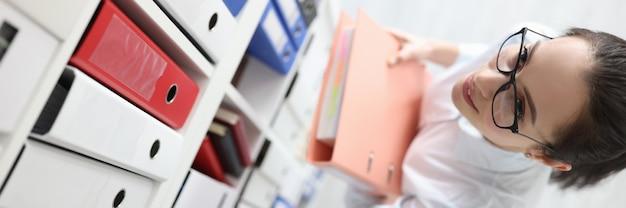Jonge vrouwelijke secretaresse in glazen neemt map met documenten van plank in archief