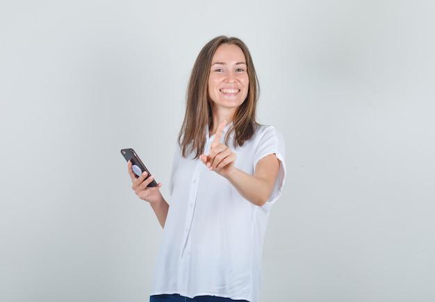 Jonge vrouwelijke smartphone houden en nee met vinger gebaren in wit overhemd