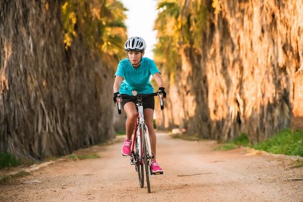 Jonge vrouwelijke sportieve fietser berijdende fiets op weg met palmen