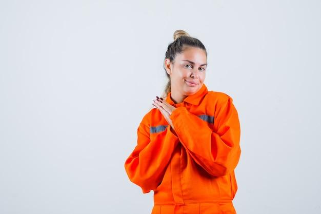 Jonge vrouwelijke staande met het combineren van handen in uniform werknemer en op zoek geliefd, vooraanzicht.