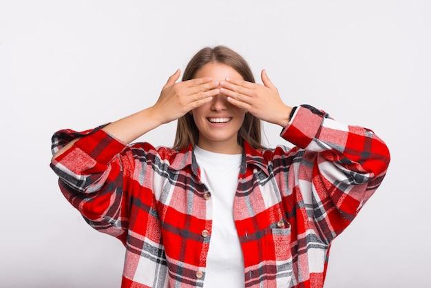 Jonge vrouwelijke student bedekt haar ogen met handen, terwijl ze naar de camera glimlacht.