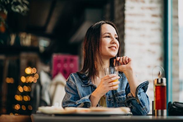 Jonge vrouwelijke student die aan laptop in bar werkt en pizza eet