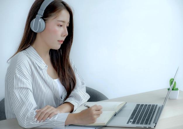 Jonge vrouwelijke student die aantekeningen maakt, kijkt naar laptop, studeert online klas, videoconferentie, e-learningcursus