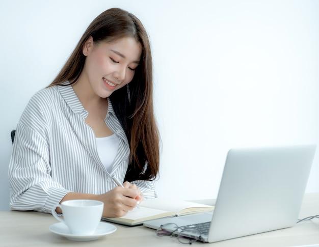 Jonge vrouwelijke student die aantekeningen maakt terwijl hij naar een laptop kijkt die online klasvideoconferentie vanuit huis bestudeert.