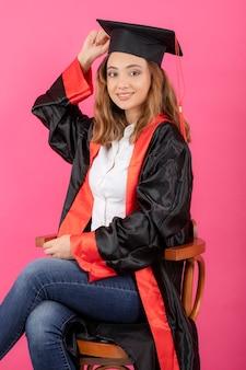Jonge vrouwelijke student die afstudeertoga draagt en op een stoel op roze muur zit.