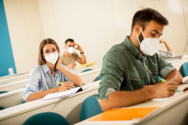 Jonge vrouwelijke student die gezicht beschermend medisch masker draagt voor virusbescherming bij collegezaal