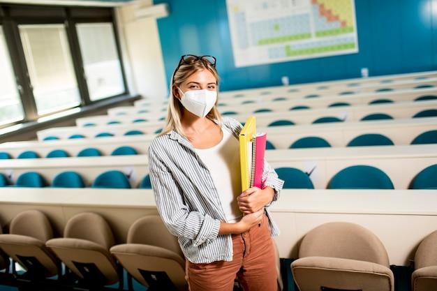 Jonge vrouwelijke student die gezicht beschermend medisch masker draagt voor virusbescherming die zich bij collegezaal bevindt
