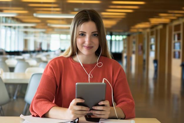Jonge vrouwelijke student die in de bibliotheek bestudeert.