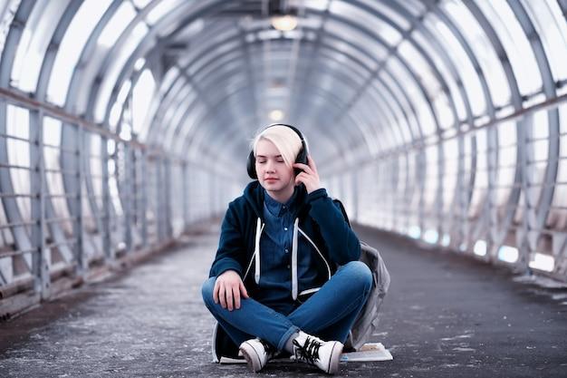 Jonge vrouwelijke student die naar muziek luistert in grote koptelefoons in de metrotunnel