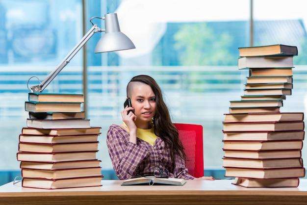 Jonge vrouwelijke student die op mobiele telefoon spreekt
