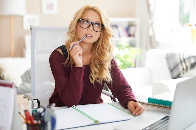 Jonge vrouwelijke student die over huiswerk denkt