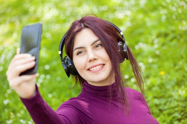Jonge vrouwelijke student die selfie met mobiele telefoon neemt
