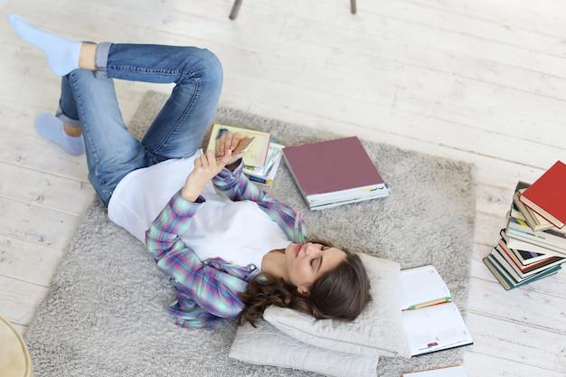 Jonge vrouwelijke student die sociale media controleert voordat ze weer gaat studeren, liggend op de vloer tegen een gezellig interieur, omringd met stapel boeken.