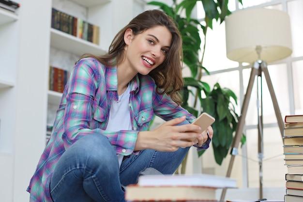 Jonge vrouwelijke student die sociale media controleert voordat ze weer gaat studeren, zittend op de vloer tegen een gezellig interieur, omringd met stapel boeken.