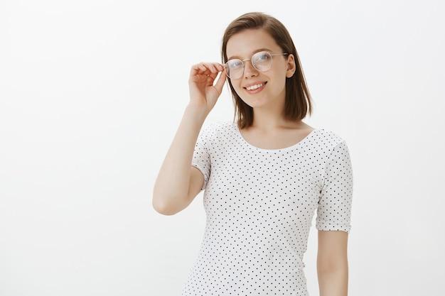 Jonge vrouwelijke student die tevreden en zelfverzekerd kijkt, een bril draagt