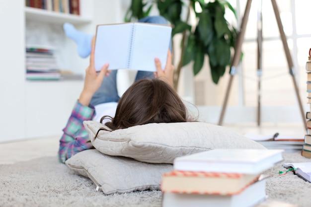 Jonge vrouwelijke student die thuis studeert, zich voorbereidt op universitaire examens, op de vloer ligt tegen een gezellig interieur, omringd met stapel boeken.