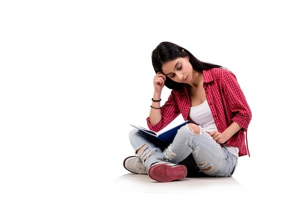 Jonge vrouwelijke student die voor examens voorbereidingen treft