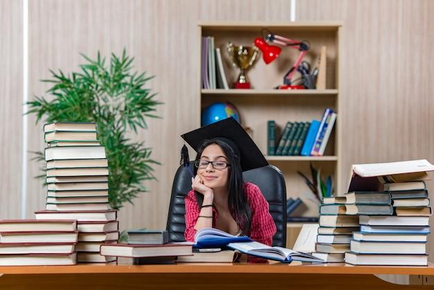 Jonge vrouwelijke student die voor universiteitsschoolexamens voorbereidingen treft