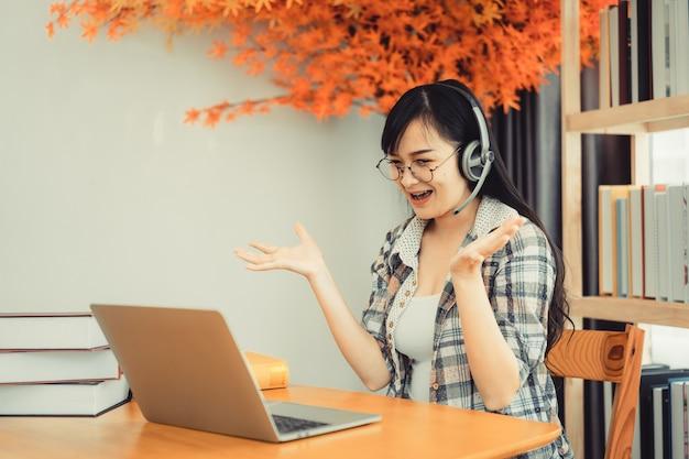 Jonge vrouwelijke student in geruit hemd zittend aan tafel met laptop tijdens het studeren.