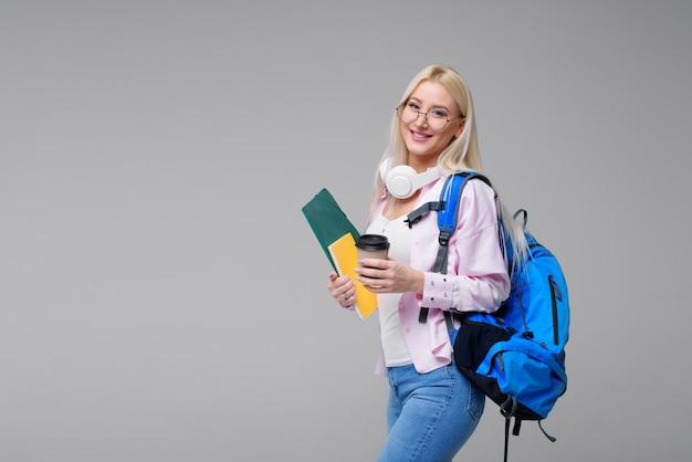 Jonge vrouwelijke student in koptelefoon met rugzak koffie drinken, glimlachend. startup, freelancer. online vreemde talen leren, examenvoorbereiding