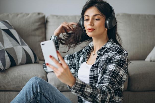 Jonge vrouwelijke student luisteren muziek via de telefoon op de koptelefoon