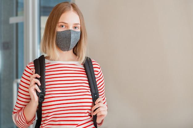 Jonge vrouwelijke student met beschermend medisch masker. portret van blonde vrouwelijke student girl aan de universiteit tijdens coronavirus covid lockdown met kopieerruimte.