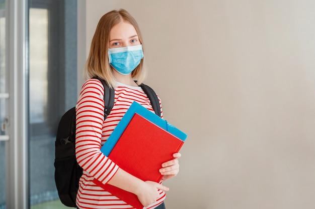 Jonge vrouwelijke student met beschermend medisch masker. portret van blonde vrouwelijke student meisje aan universiteitsinterieur tijdens coronavirus covid 19 lockdown met kopieerruimte