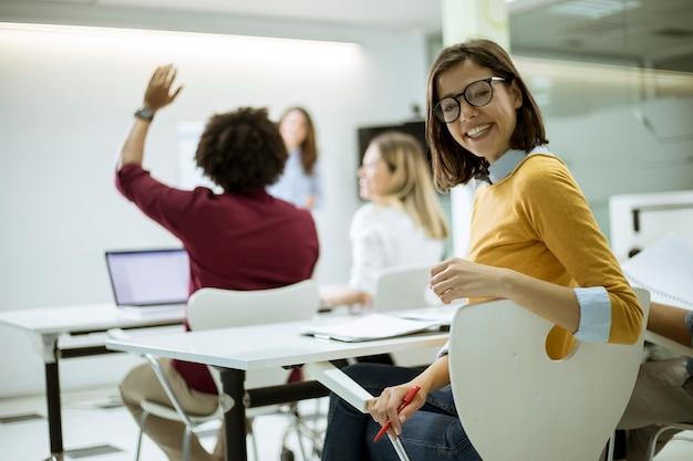 Jonge vrouwelijke student met bril in de klas